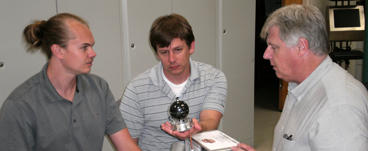 Dr. Eric Benton (right) works with graduate students on his radiation detector.